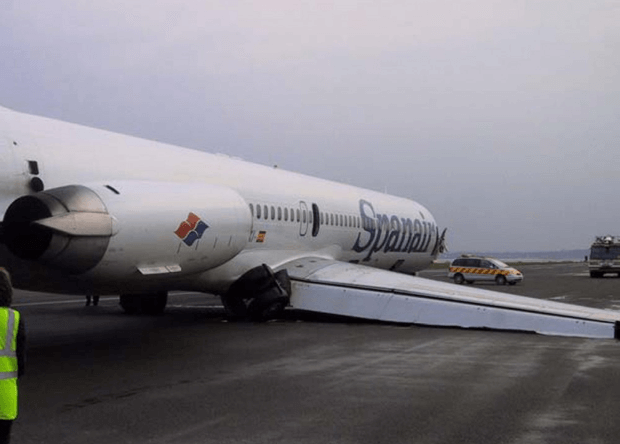 grounded commercial plane with its wings dipped to the ground