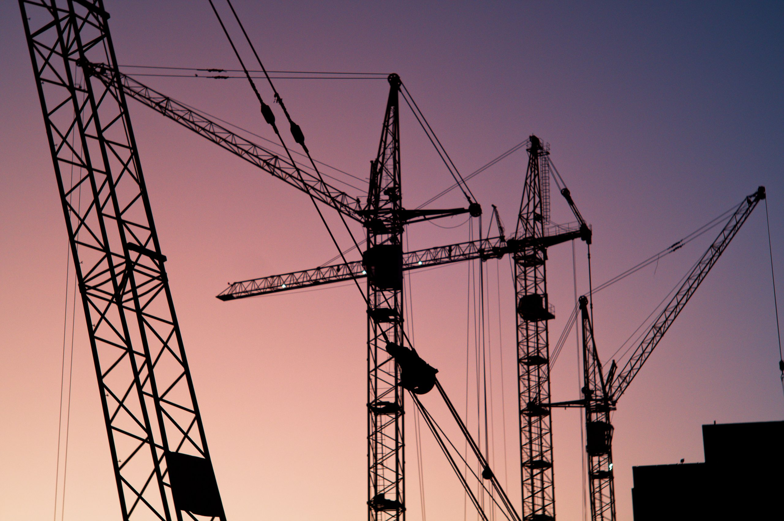 silhouette of construction cranes