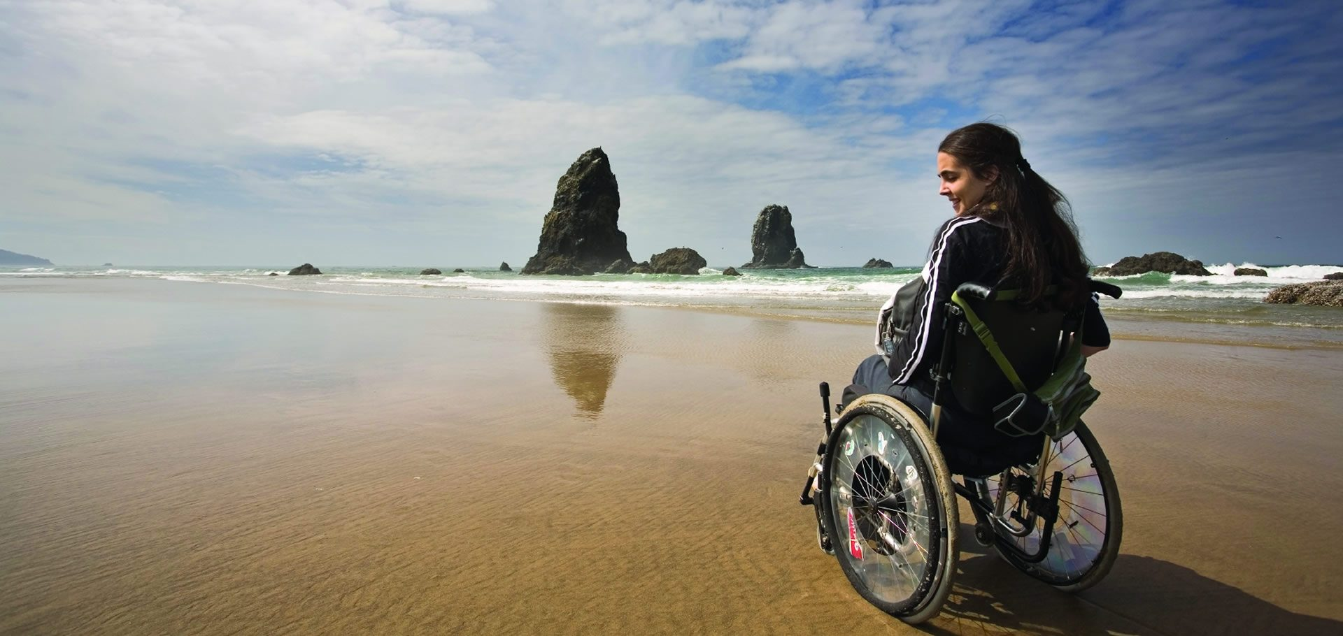a woman on a wheelchair sitting near the shore