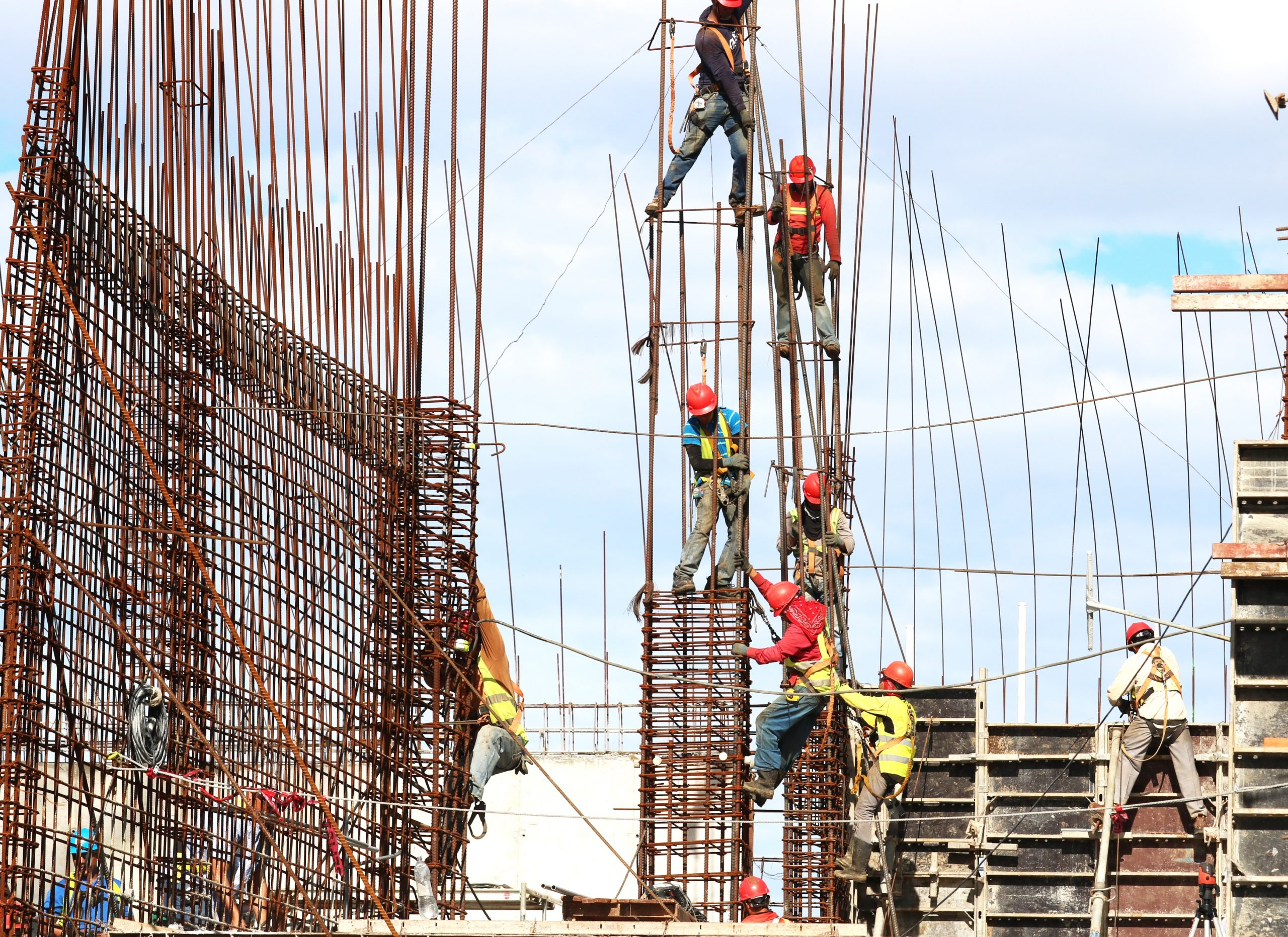 construction workers climbing a rebar pole