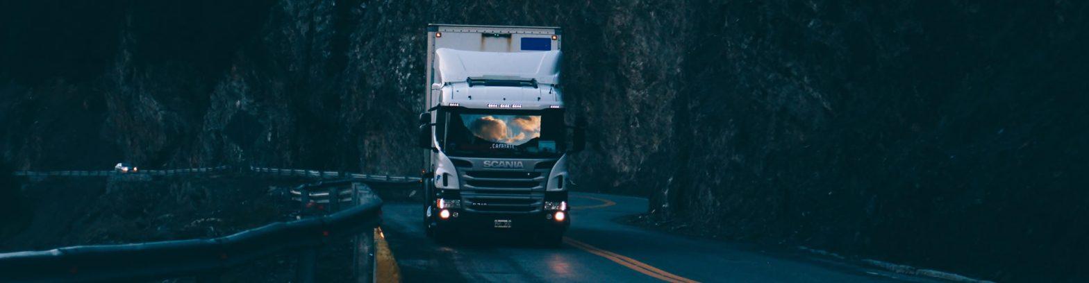 a truck driving beside a cliff